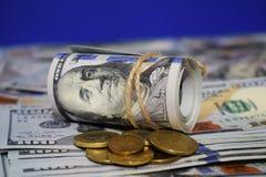 En rulle av dollar på bakgrunden av spritt hundra dollarräkningar och olika mynt arkivbild
