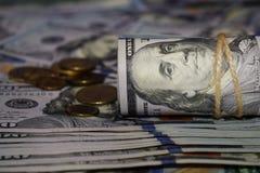 En rulle av dollar på bakgrunden av spritt hundra dollarräkningar och olika mynt arkivfoton