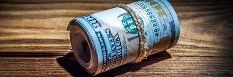 En rulle av dollar på en trätexturerad tabell i mörkret som är upplyst vid en stråle av ljus royaltyfria foton