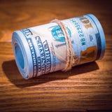 En rulle av dollar på en trätexturerad tabell i mörkret som är upplyst vid en stråle av ljus royaltyfri fotografi