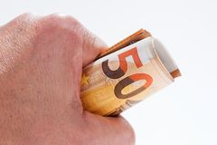 En rulle med femtio eurosedlar i handen Arkivbild