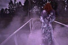 En ruskig illavarslande kvinna står på bron på natten i en dimma fotografering för bildbyråer