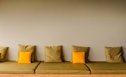 En ryggl?s platssoffa med fem fyrkantiga kaki- kuddar och tv? ljusa gula kuddar kopiera avst?nd fotografering för bildbyråer