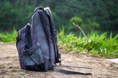En ryggsäck på en jordning med naturbakgrund royaltyfri foto