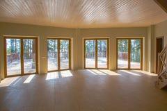 En rymlig korridor i ett trähus med stora fönster i trät Royaltyfria Bilder