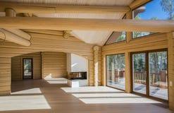 En rymlig korridor i ett trähus med stora fönster i trät Arkivfoton