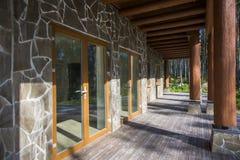 En rymlig terrass av ett trähus i en skog med stor vind Arkivbild