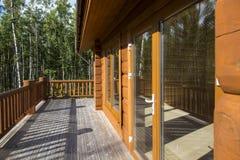 En rymlig terrass av ett trähus i en skog med stor vind Fotografering för Bildbyråer