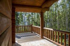 En rymlig terrass av ett trähus i en skog med stor vind Arkivfoto