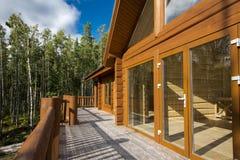 En rymlig terrass av ett trähus i en skog med stor vind Arkivfoton