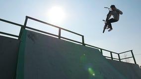 En ryttare för professionell BMX i den gråa hoodien som utför ett trick på rampen arkivfilmer