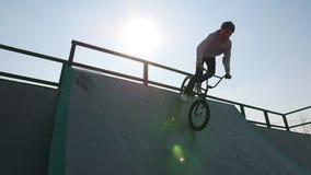 En ryttare för professionell BMX i grå hoodie som rider ner på rampen i skateparken arkivfilmer