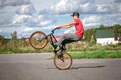 En ryttare på en cykel gör trick royaltyfri fotografi