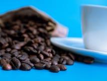 En säck av den naturliga kaffebönan sätter bredvid det svarta kaffet i ett vitt keramiskt exponeringsglas royaltyfria foton