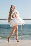 En säker kvinna på en bakgrund för blå himmel En lycklig dam i en vit klänning En sommarsemester En flicka på en rymlig terrass Arkivbilder