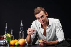 En säker ung man som dricker en whisky eller en tequila i en klubba på en svart bakgrund En framgångaffärsman som vilar en bar Arkivfoto