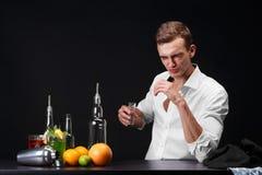 En säker ung man som dricker en whisky eller en tequila i en klubba på en svart bakgrund En framgångaffärsman som vilar en bar Royaltyfri Foto