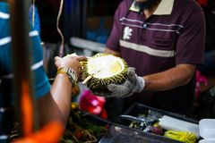 En säljare som visar durianfrukten till den turist- durianen - en exotisk frukt med en mycket otrevlig och skarp lukt säljs på arkivbild