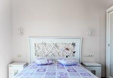 En säng i ett sovrum Huvudgavel- och lilakuddar Två sängkant t arkivfoton