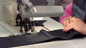 En sömmerska syr torkdukar i tygatelierproduktionslinje Slut upp av en symaskin arkivfilmer