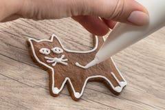En söt katt för handmålning genom att använda en isläggningpåse med sockerglasyr på kaka arkivbilder