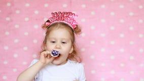 En söt liten flicka som blåser det horn- partiet, leende, har gyckel, skrattar och firar lycklig födelsedag lyckönskan Närbild arkivfilmer