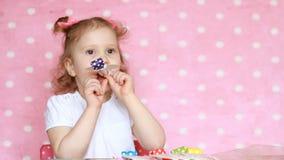 En söt liten flicka som blåser partihorn, leende, har gyckel, skrattar och firar lycklig födelsedag Närbildståendebarn lager videofilmer
