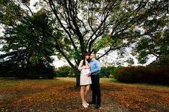En s'attendant à des couples heureux enceintes tenant le charbon de bois vide embarquez dans la forme du coeur Photos libres de droits
