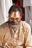 En sadhu som läser en hinduisk scripture arkivfoto