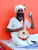 En sadhu som spelar musik och sjungande religiös sång på den stora kumbhmelaen 2016, Ujjain Indien Arkivbild