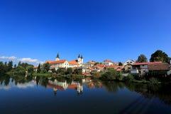En sagaslott och en gammal stadstad med lakesidespegelreflexion i Telc, Tjeckien Arkivfoton