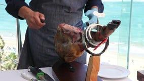 En sakkunnig man som klipper Iberican skinka stock video