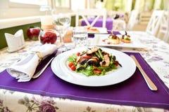 En sallad i vårrestaurang med violetta servetter Royaltyfria Bilder