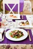 En sallad i vårrestaurang med violetta servetter Arkivfoton