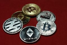 En samling av cryptocurrencymynt p? en r?d bakgrund f?r sammet royaltyfri bild