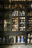 En samling av keramik är utsatt i ett skärmkabinett i ett museum i Hoi An (Vietnam) Arkivfoto