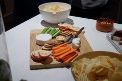 En samling av ostar och mellanmål på ett uppläggningsfat royaltyfri fotografi