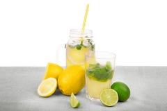 En sammansättning av den mogna gula citronen som är ljusa - gräsplanlimefrukter och ny mintkaramell på en grå tabell som isoleras Arkivbilder