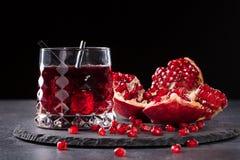 En sammansättning av en granatäppledrink och en klippt granatrött på en svart bakgrund Healthful och nya röda coctailar arkivbild