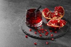 En sammansättning av en granatäppledryck och en klippt granatrött på ett mörker - grå bakgrund Healthful, naturlig ny röd fruktsa royaltyfri fotografi