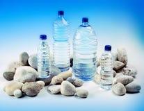 En sammansättning av härliga flodstenar och flaskor av mineral w Royaltyfria Bilder
