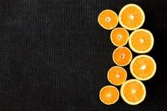 En sammansättning av snittet i halvaapelsiner och tangerin på en svart bakgrund Arkivfoton