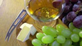 En sammansättning med ett exponeringsglas av ost för konjakdruvabrie stock video