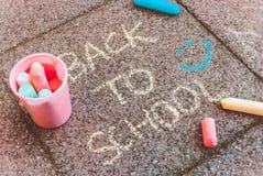 En sammansättning med en hink av färgrika chalks och chalks som ligger på trottoar runt om 'baksida till skola'text Lyckli royaltyfria bilder