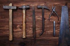 En sammansättning av gamla carpenter'shjälpmedel på träbakgrund Arkivbild