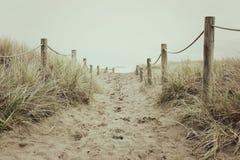 En sandig och Roped bana leder till stranden arkivfoton