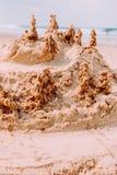 En sandslott på en sandig strand, uppsättning mot en ljus blå sommarhimmel royaltyfri fotografi