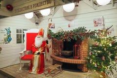 En Santa Claus i hans hussammanträde i hans stora röda stol nära en spis arkivfoton