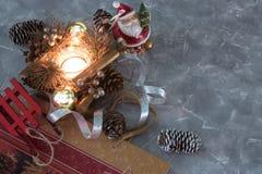 En Santa Claus leksak, en brinnande stearinljus och en släde lycklig flicka med loppfallet uppsättning av julpynt på betong med k royaltyfria bilder