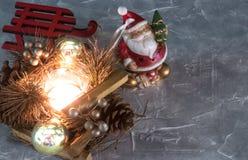 En Santa Claus leksak, en brinnande stearinljus och en släde lycklig flicka med loppfallet uppsättningen av julprydnader på grå f arkivfoto